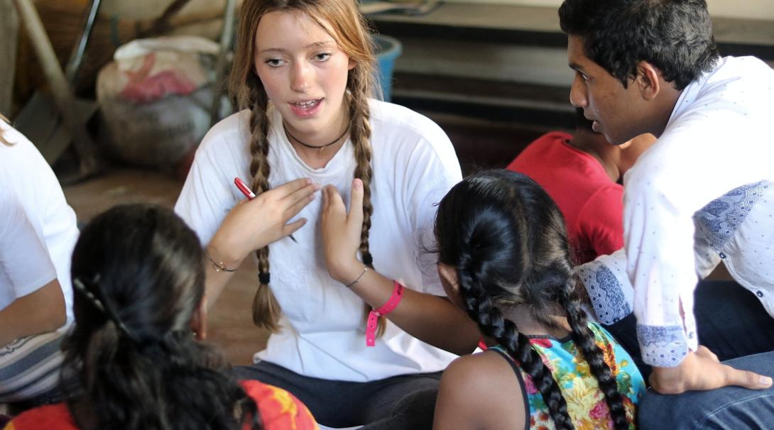 Teenage volunteer teaches English to the students in her class in Sri Lanka